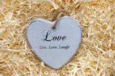 Single grey wooden heart in a love nest — ストック写真