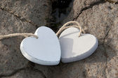Wooden love hearts on the sand bank — Stock Photo