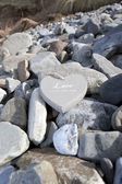 Loveing wooden heart on the rocks — Stock Photo