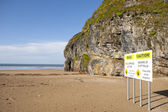 Beach cliff falls warning sign — Stock Photo