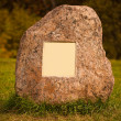 Big granite rock with empty metal plate - Stock Photo