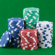 Poker chips on green playing table background - Stock Photo