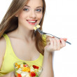 Portrait of a pretty young woman eating fruit salad — Stock Photo #13896075