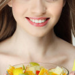 Portrait of a pretty young woman eating fruit salad — Stock Photo #13896093