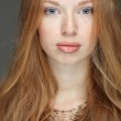 Closeup portrait of sexy redheaded young woman with beautiful blue eyes on white background — Stock Photo