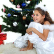 Little beautiful girl near a christmas tree isolated on a white background — Stock Photo #17131221