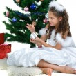 Little beautiful girl near a christmas tree isolated on a white background — Stock Photo #17131229