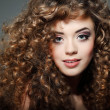 Young beautiful woman with long curly hairs — Stock Photo #18973653