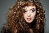 Young beautiful woman with long curly hairs — Stok fotoğraf