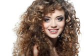Young beautiful woman with long curly hairs on a white background — Stock Photo