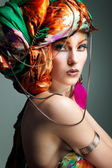 A photo of beautiful redheaded girl in a head-dress from the coloured fabric, glamour — Stock Photo