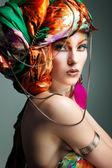 Een foto van prachtige roodharige meisje in een hoofd-jurk van de gekleurde stof, glamour — Stockfoto