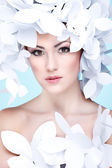 Wonderful girl in a hat from paper white butterflies. On a blue background. Beauty Face — Stock Photo
