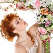 Royalty-Free Stock Photo: Beautiful redheaded girl with the bouquet of tulips, which stands in a gold frame, flowered, isolated on a white background