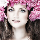 Beautiful young girl with pink flowers — Stock Photo