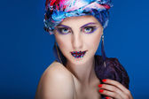 A photo of beautiful girl in a head-dress from the coloured fabric,on a blue background, glamour — Stock Photo