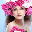 Beautiful young girl with pink flowers on a blue background — Stock Photo