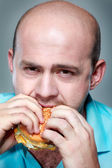Funny man eating hamburger on grey background — Stock Photo