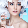Wonderful girl in a hat from paper white butterflies. On a blue background. Beauty Face — Stock Photo #31188763