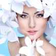 Wonderful girl in a hat from paper white butterflies. On a blue background. Beauty Face — Stock Photo #31188823