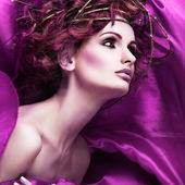 Red hairs. Portrait of beautiful girl in violet fabric in a chaplet from branches. — Stock Photo