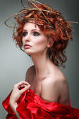 Red hairs. Portrait of beautiful girl in red fabric in a chaplet from branches. — Stock Photo