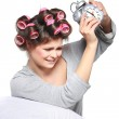 Happy positive young woman waking up and switching off the alarm clock — Stock Photo #36542893