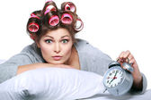 Happy positive young woman waking up and switching off the alarm clock — Stock Photo