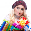 A photo of beautiful girl is in winter clothes with varicoloured gift boxes, isolated — Stock Photo #36802277