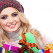 A photo of beautiful girl is in winter clothes with varicoloured gift boxes, isolated — Stock Photo