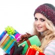 Stock Photo: A photo of beautiful girl is in winter clothes with varicoloured gift boxes, isolated