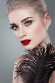 Closeup portrait of sexy whiteheaded young woman with black feather on grey background — Stock Photo