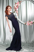 Beautiful sexual redheaded girl in evening dress with the hoop with pink flowers — Stock Photo
