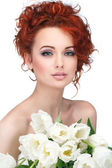 Beautiful young redheaded girl with white tulips, isolated on a  — Stock Photo