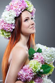 Close-up portrait of beautiful young redheaded girl in a chaplet with  flowers — Stock Photo