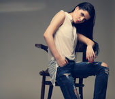 Photo of beautiful sexual brunette, sitting on a brown wooden chair, fashion style, glamour — Stock Photo