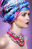 A photo of beautiful  girl in a head-dress from the coloured fabric,on a violet background,  glamour — Stock Photo