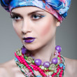 A photo of beautiful girl in a head-dress from the coloured fabric,on a grey background, glamour — Stockfoto #46288589