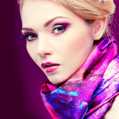 Closeup portrait of sexy  young woman with beautiful blue eyes on violet background — Stock Photo