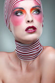 Portrait of girl with a bright theatrical make-up with the striped scarf on a head — Stock Photo