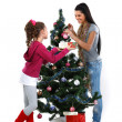 Mother and daughter near a christmas tree with gifts, isolated on a white b — Stock Photo #7828445