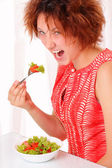Angry young girl eating tasty salad — Stock Photo
