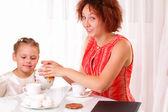 Niño bonita y hermosa joven bebiendo té — Foto de Stock