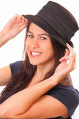 Smiling young brunette woman in a hat — Stock Photo