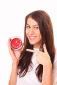 Smiling young brunette woman with alarm clock — Stock Photo