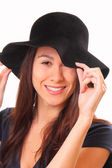 Attractive young woman in a black hat — Stock Photo