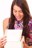 Beautiful young woman opens a holiday gift — Stock Photo