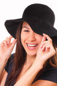 Charming and happy young woman in a black hat — Stock Photo