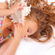 Quiet little girl with seashell — Stock Photo