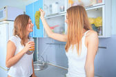 Two girl friends talk in kitchen — Stock Photo